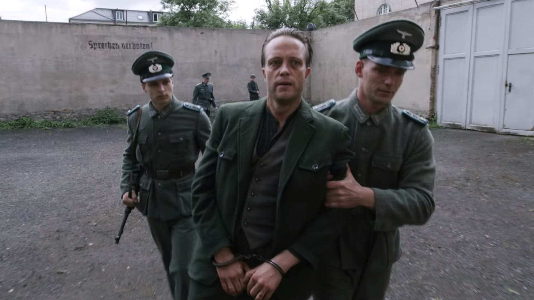 A man in a green suit, handcuffed, being escorted by two men in green military uniform.