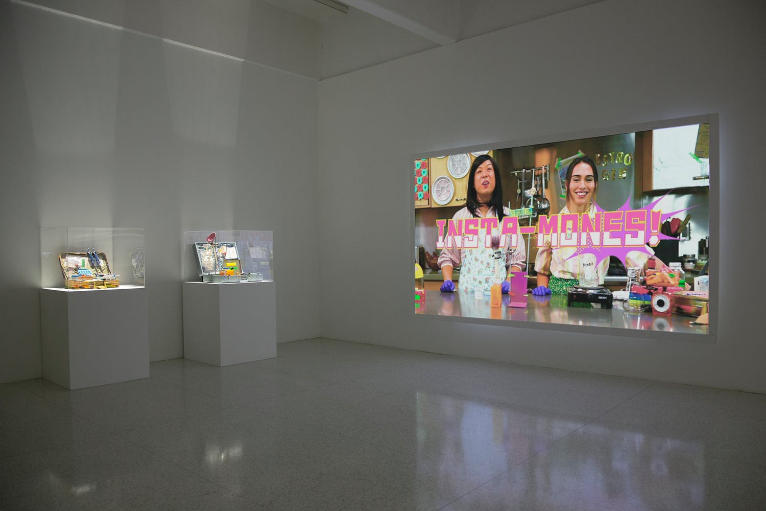 """Two pedestals and one large video projection displaying two women with the words""""Insta-Mones!"""""""