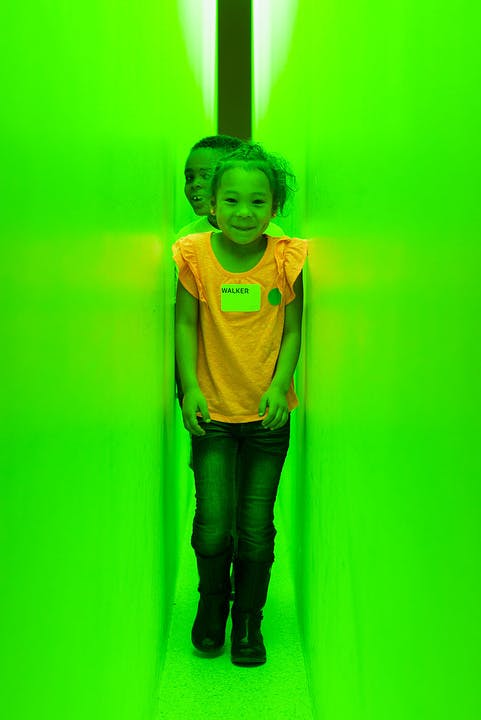 Girl standing between two narrow walls that are lit in green light.