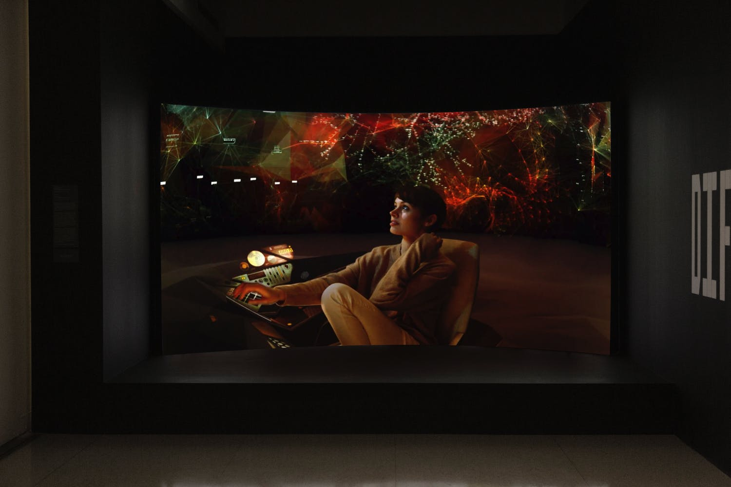 A curved video screen with a futuristic image of a woman sitting at a desk with a projection in the background