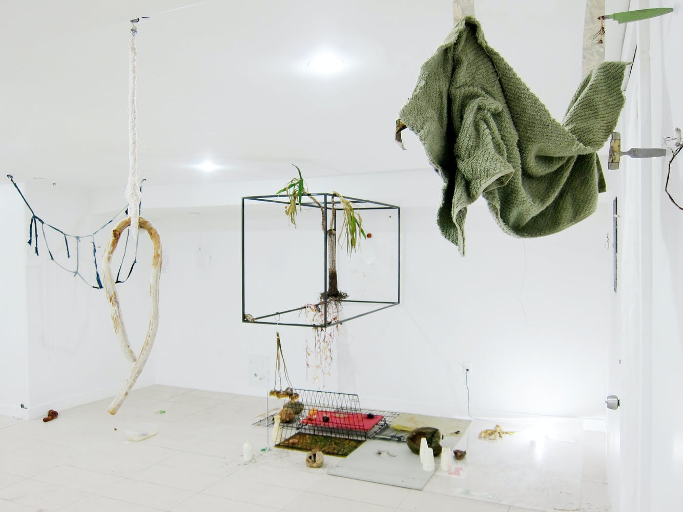 Image of various objects, frames, draped cloth hanging in a white gallery space