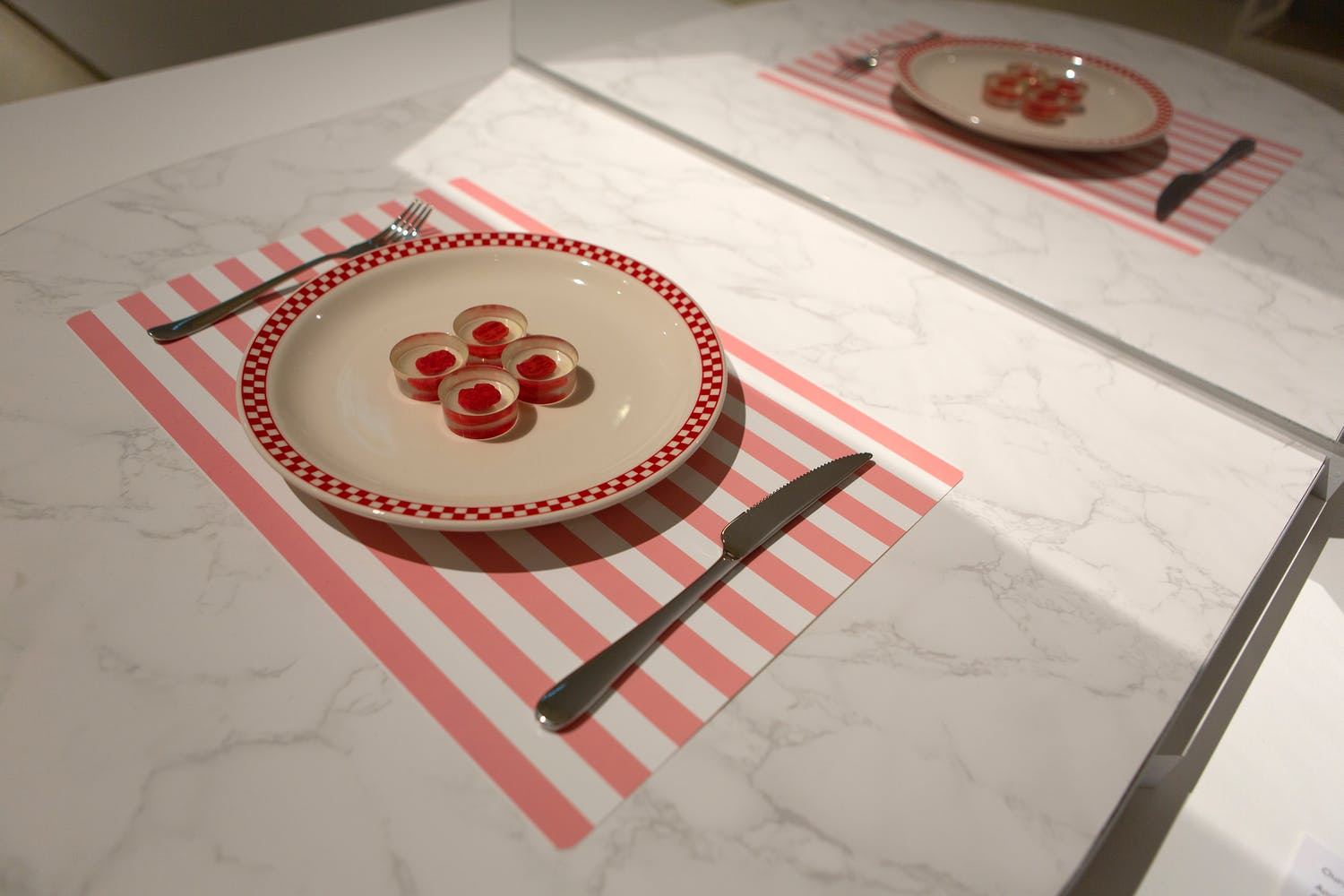 A placemat, knife and fork, and plate with four translucent disks