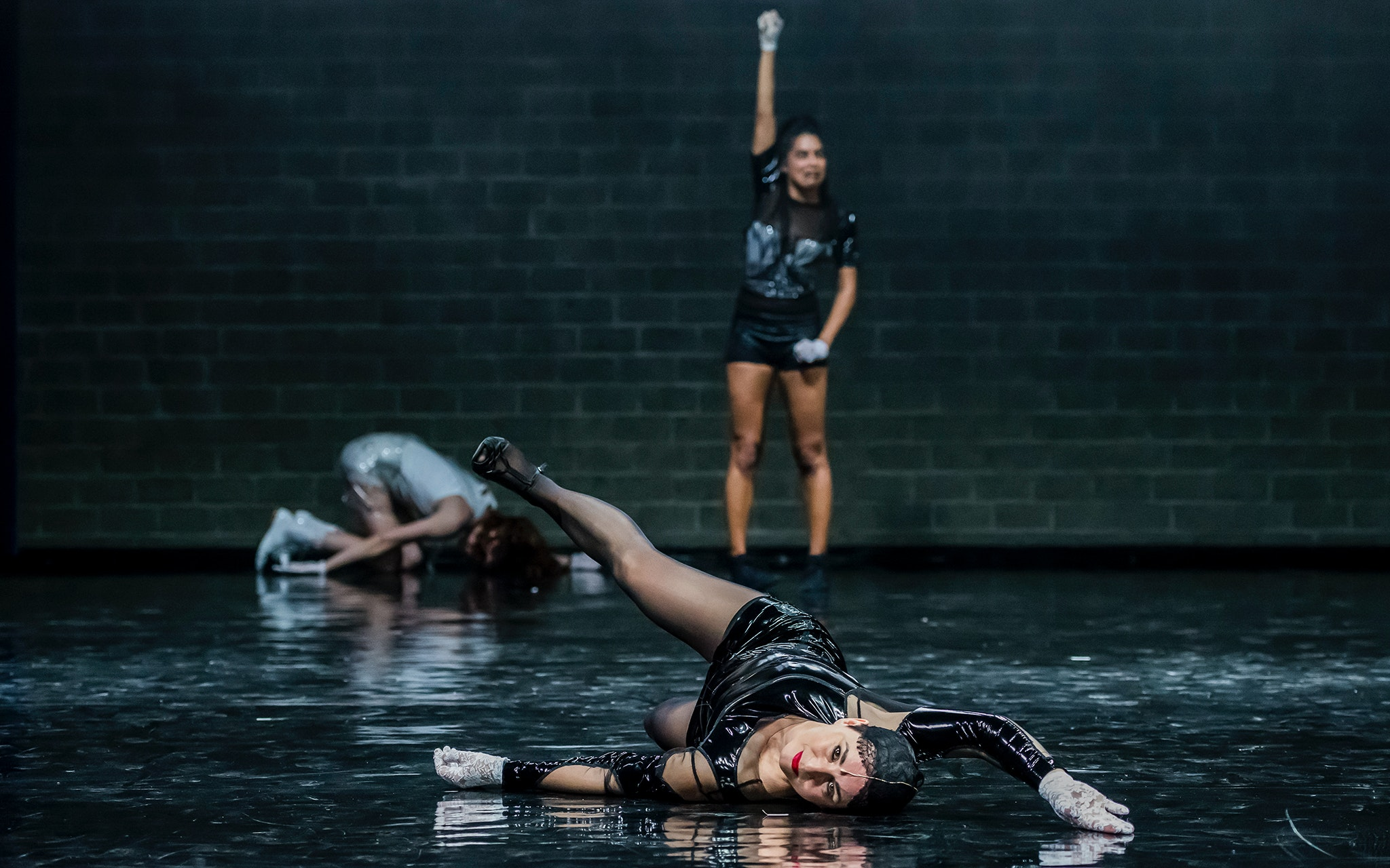Two dancers on the ground, one standing with arm raised, on a black stage with brick wall background.
