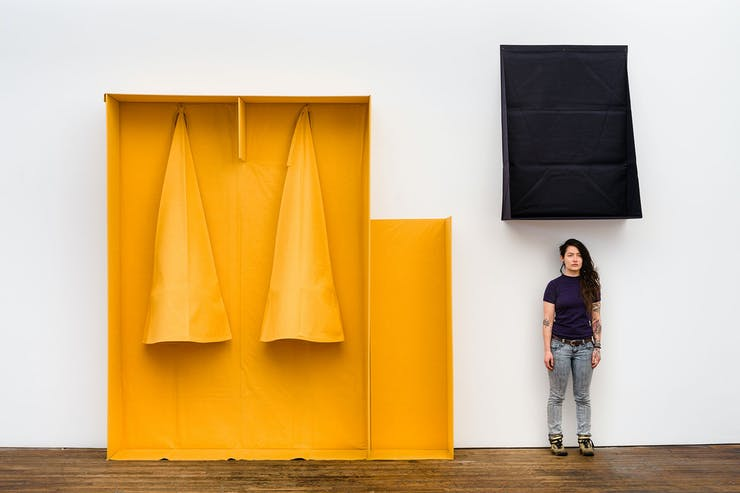 An open box made of felt with two yellow cones hanging inside is next to a black felt box with a woman in a black t-shirt and jeans standing underneath.