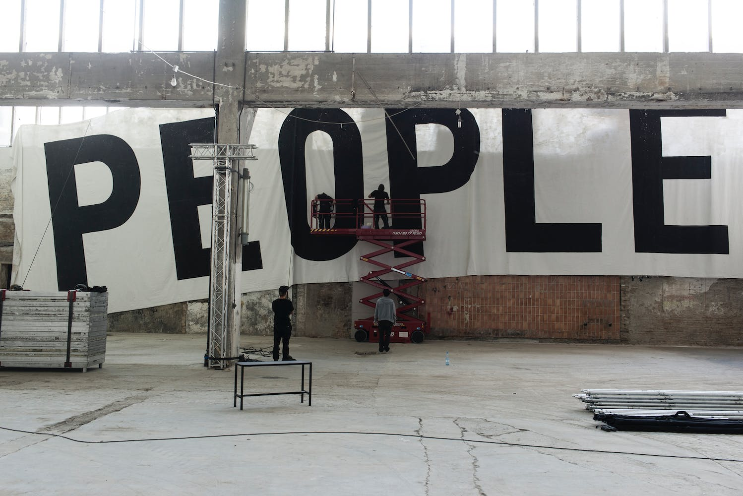 """People hanging a large scale horizontal mural cloth mural that says """"PEOPLE"""" in large black letters"""