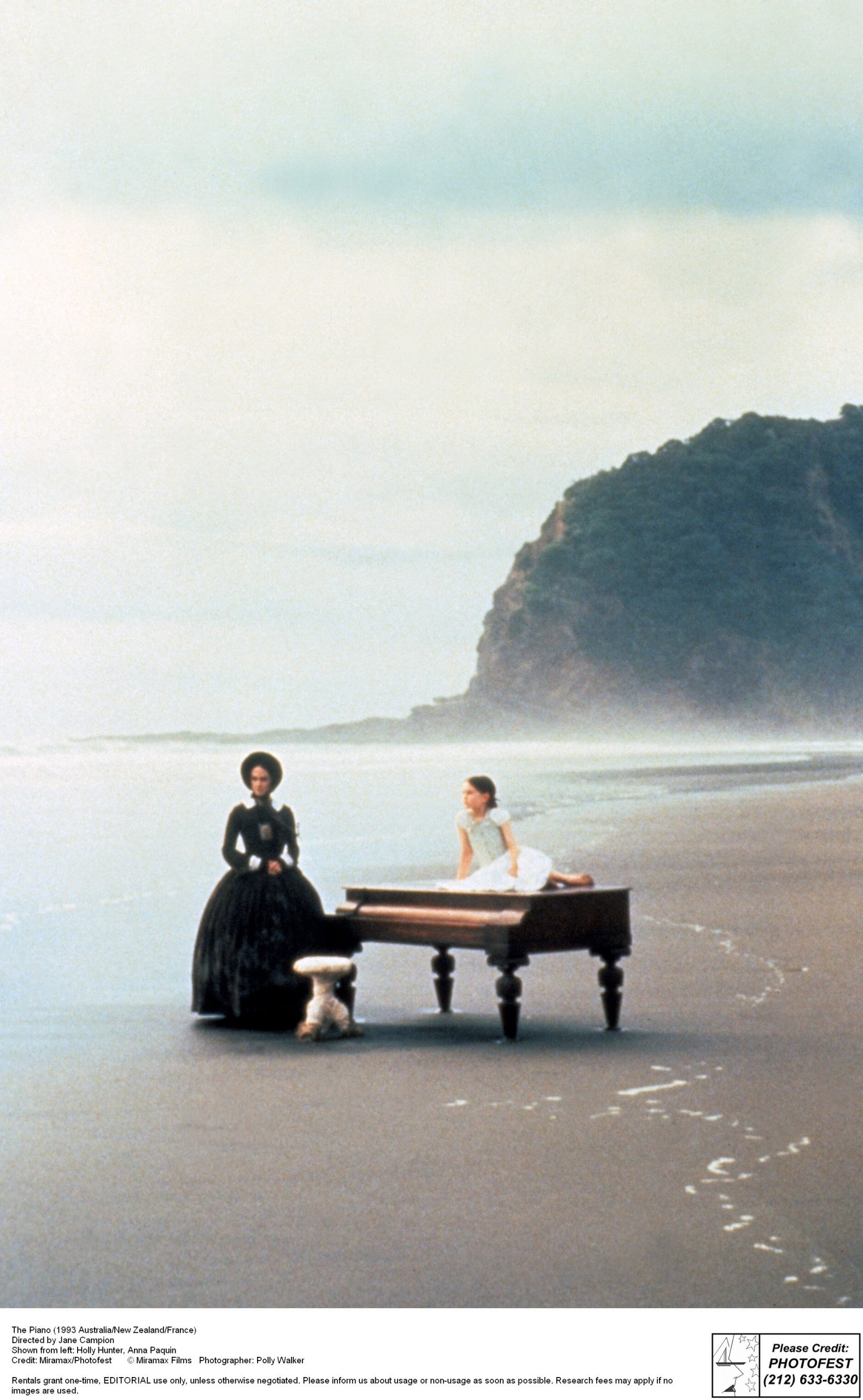A woman sits at a piano on a beach.