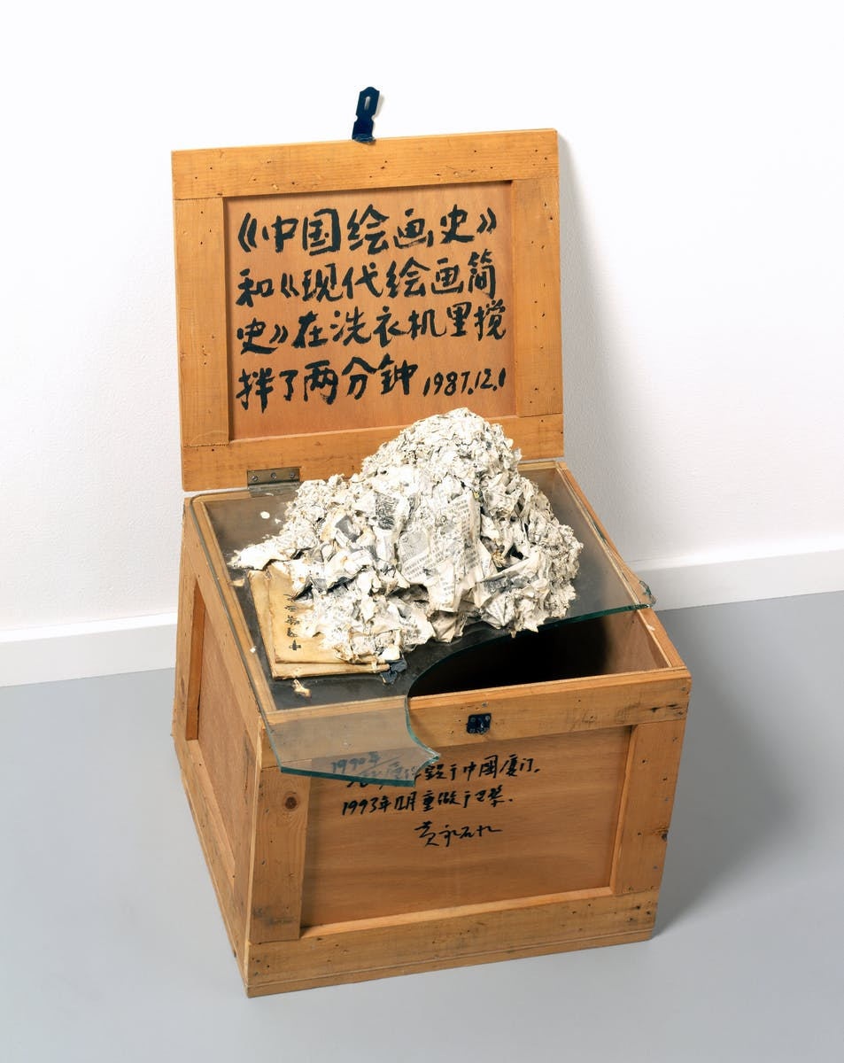 Photo of mixed media sculpture of a washing machine destroyed book on broken glass on top of a wooden crate.