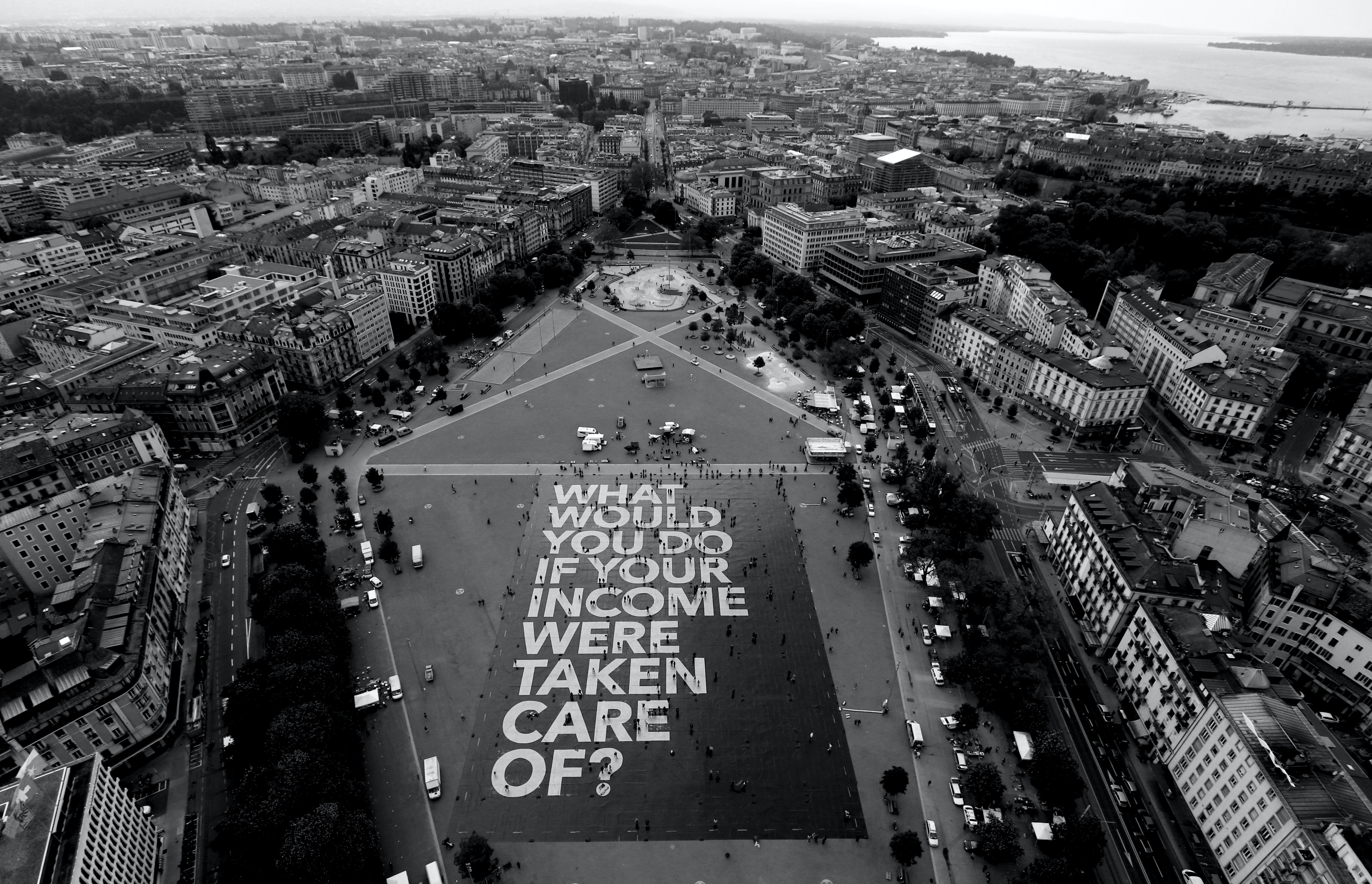 """Image of city square with giant poster on ground that reads """"What would you do if your income were taken care of?"""""""