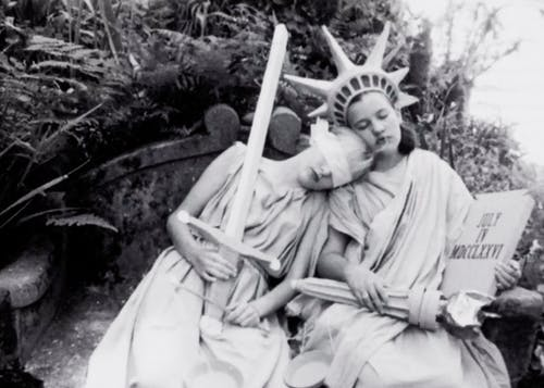 Two women sitting next to each other in togas. One wearing a blindfold holding a sword and scale, the other in the Statue of Liberty attire (crown, torch).