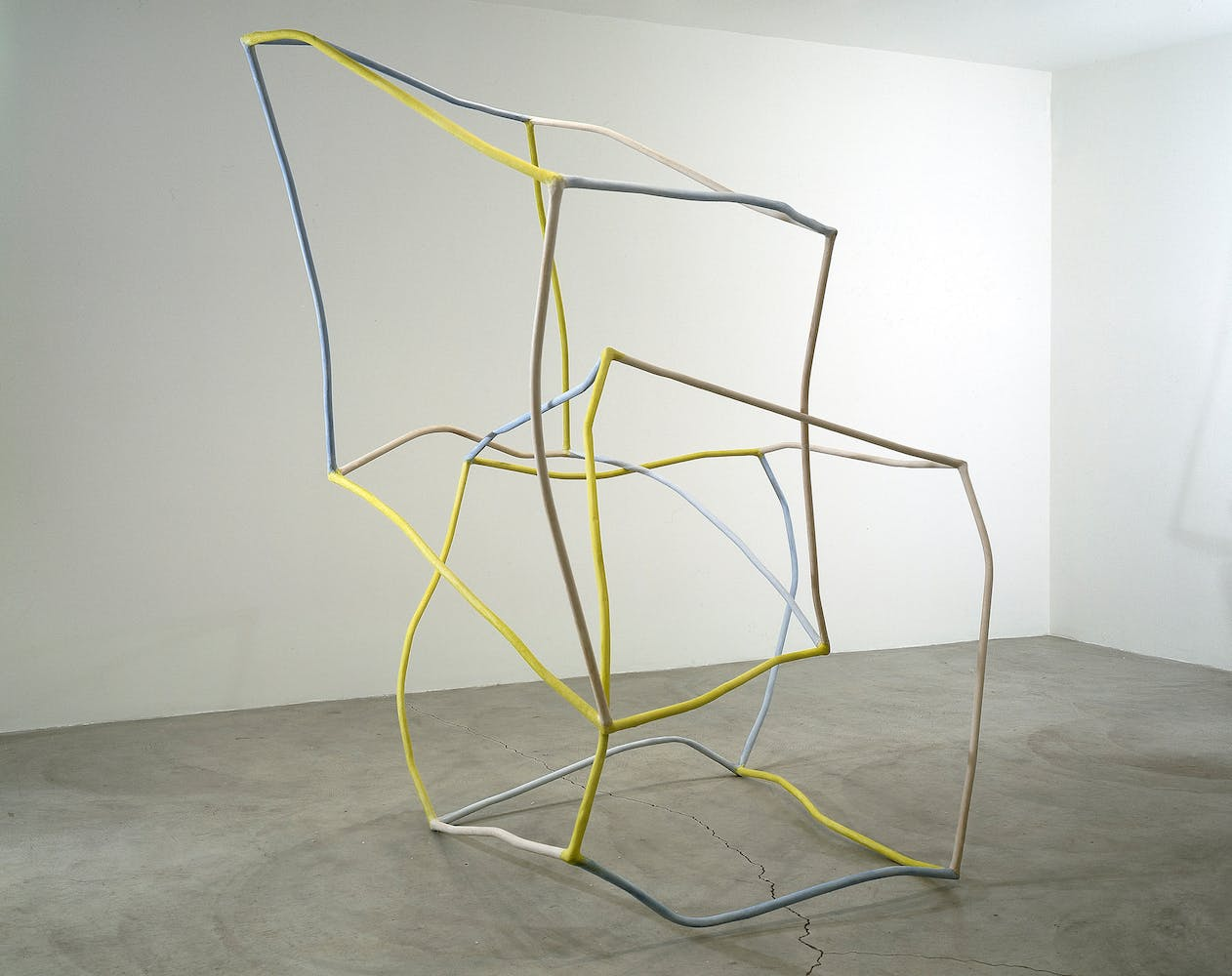 Thin crooked sculpture in the shape of two intersecting, distorted cubes in yellow and blue