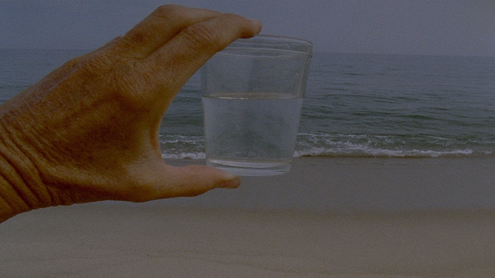 Image of hand holding glass of water on a beach with ocean in background