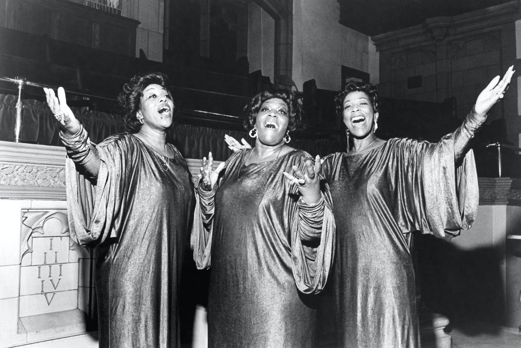 Three women in choir robes singing.