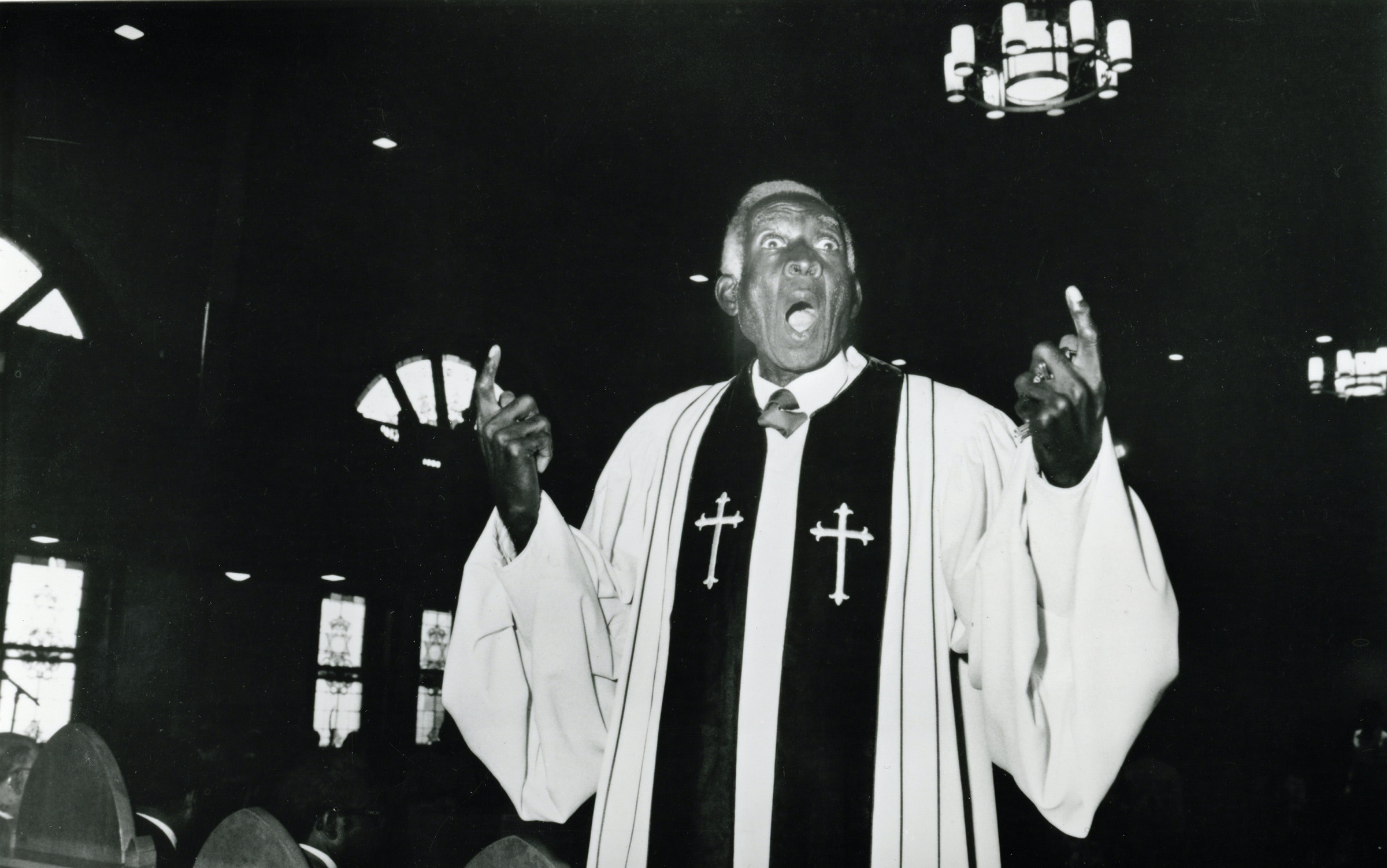 Black and white image of a pastor singing with his fingers pointed upward.