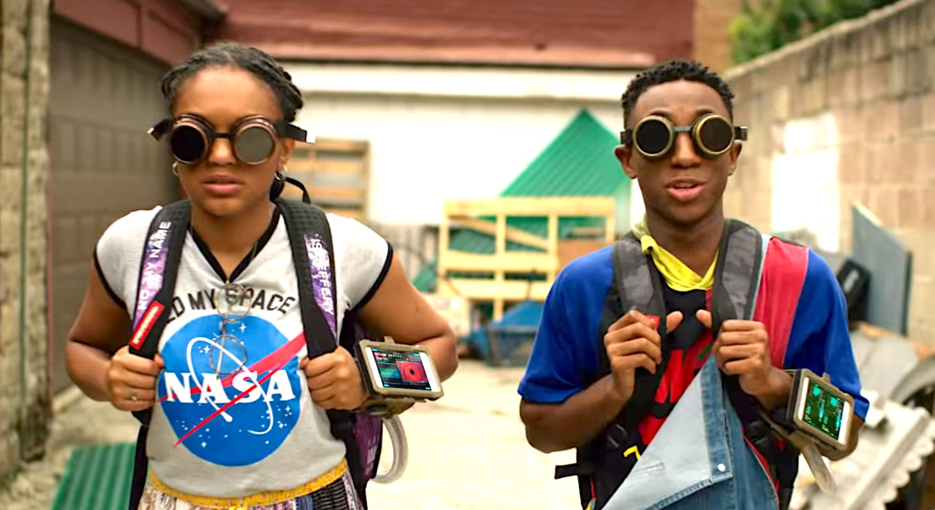 African american teen girl and boy, wearing backpacks, gogglels, and iPhones on their wrists.