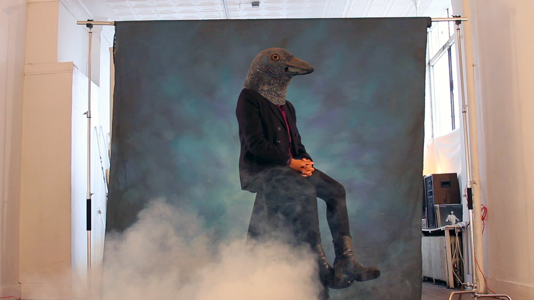 Image of person wearing crow mask with smoke in the foreground