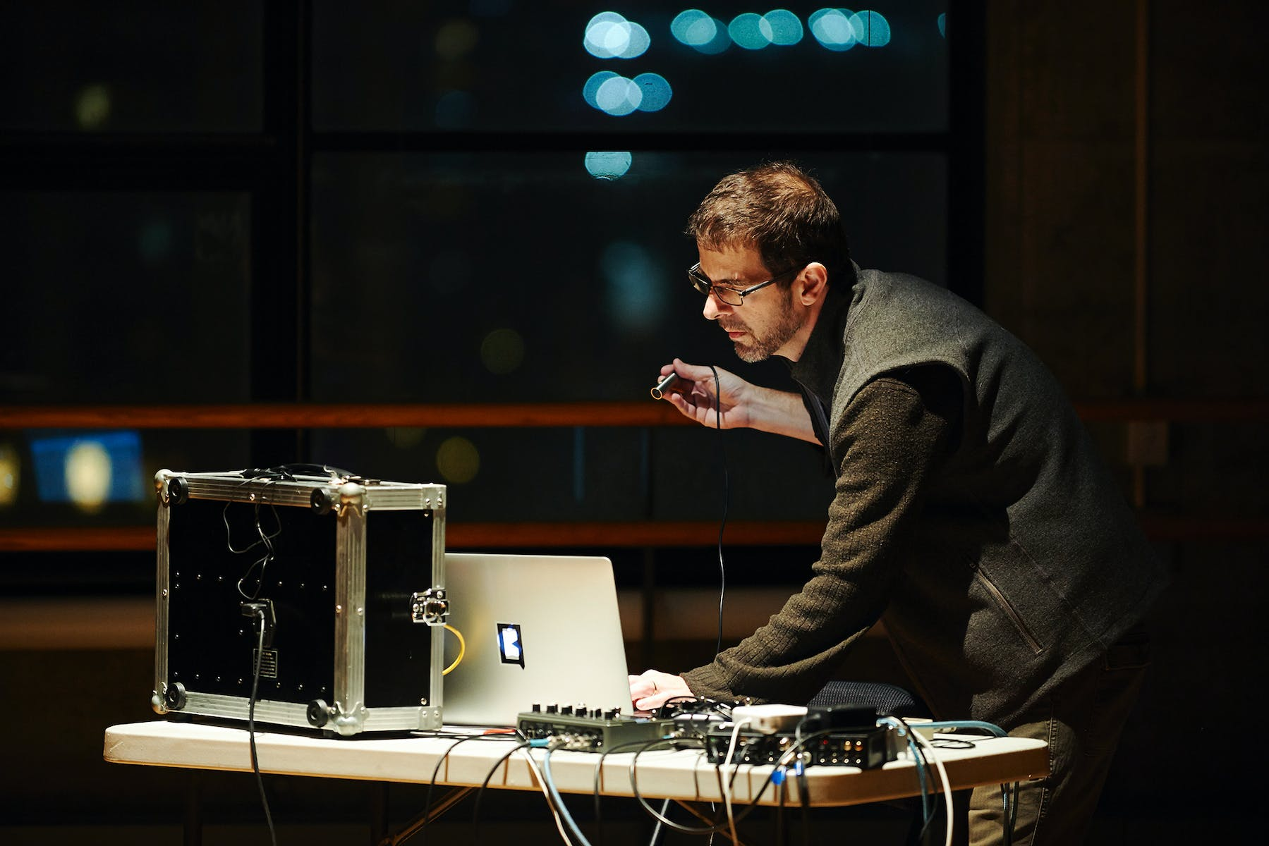 Man standing at laptop with many electric connections.