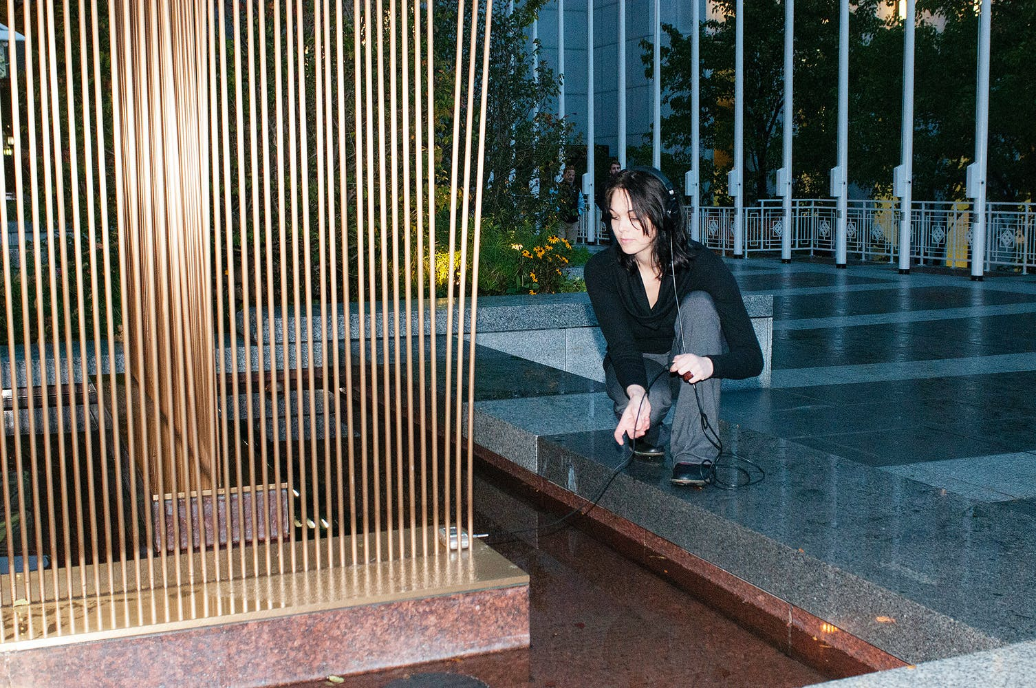 Woman leaning over metal sculpture listing to headphones.