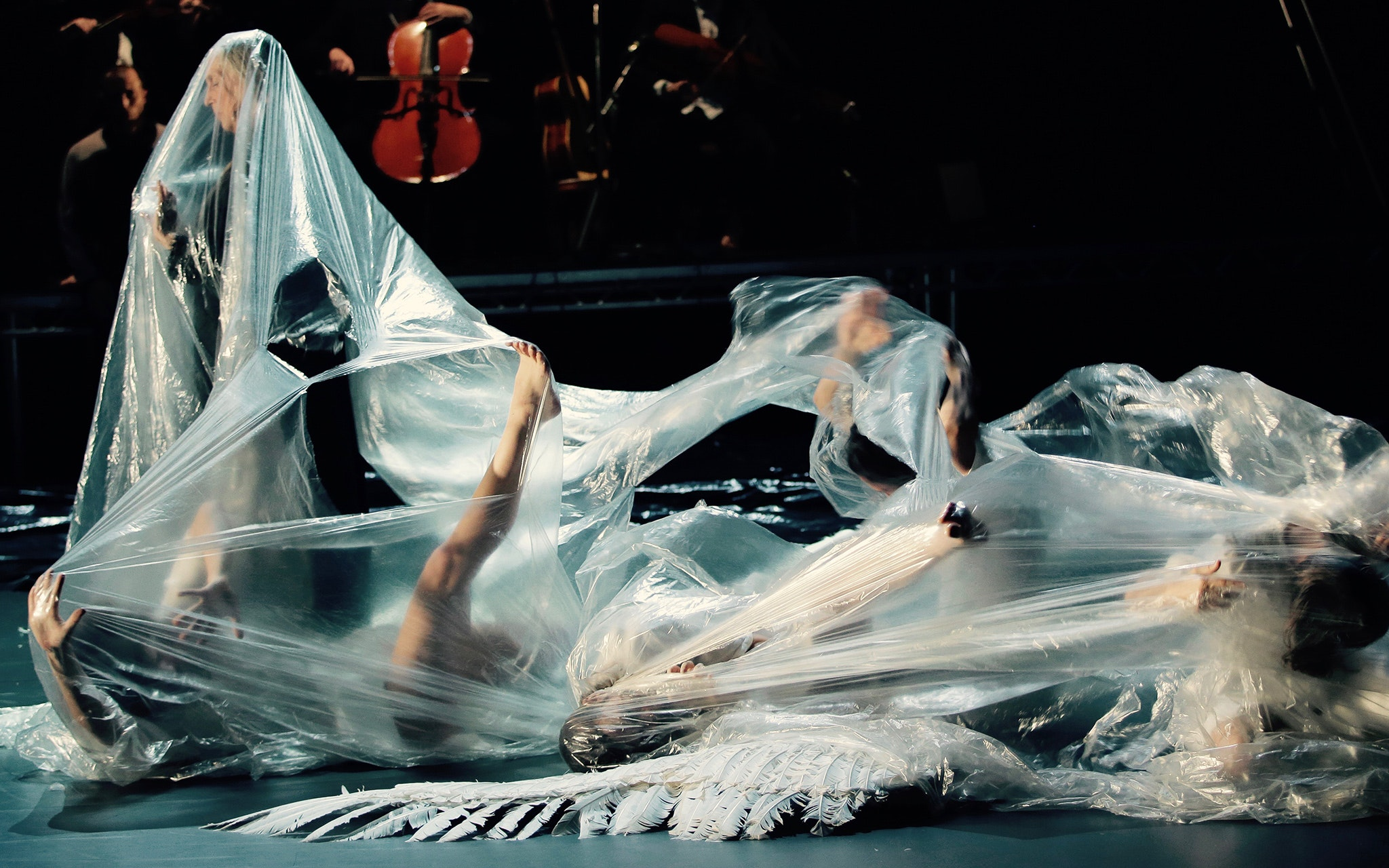 Dancers on the ground covered in plastic tarp.