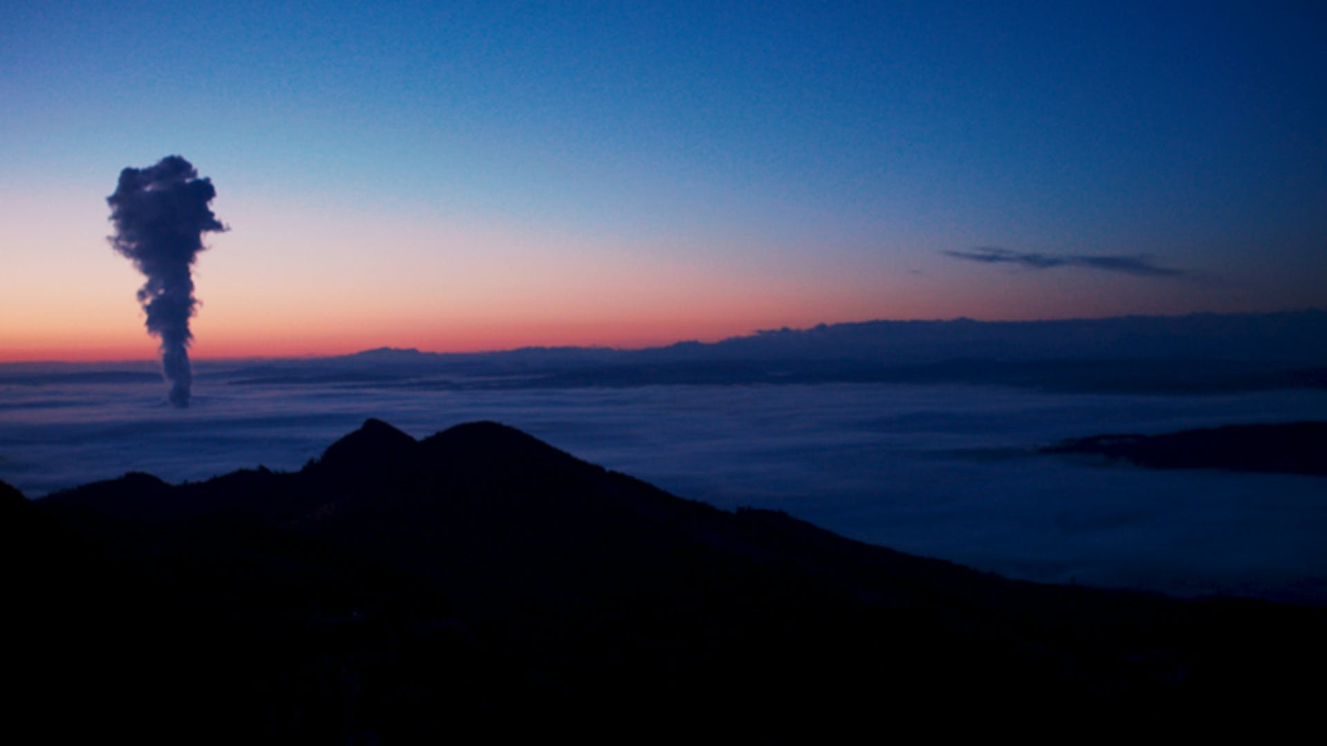 Image of sunrise with mountain in foreground