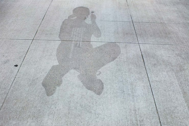 Shadow outline on sidewalk with text of Time poem.
