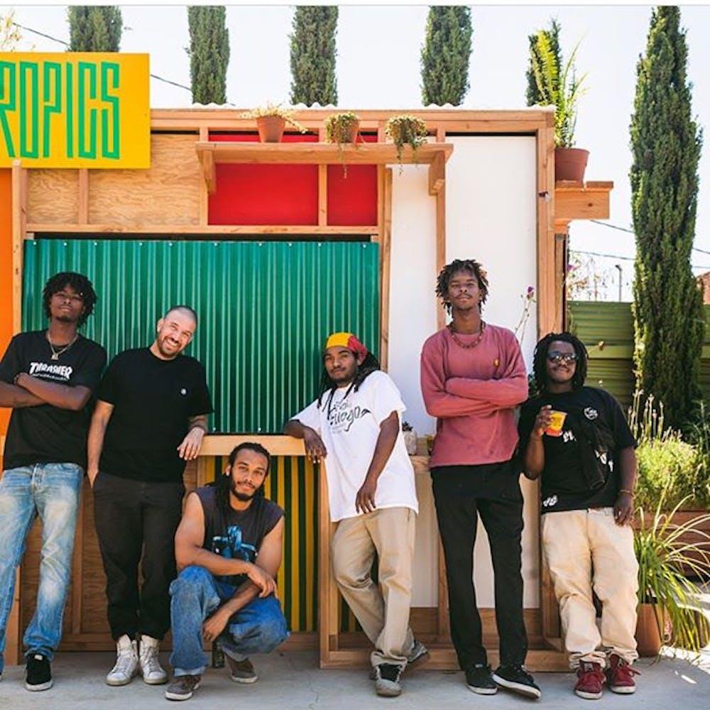 Image of six men standing outside of juice kiosk