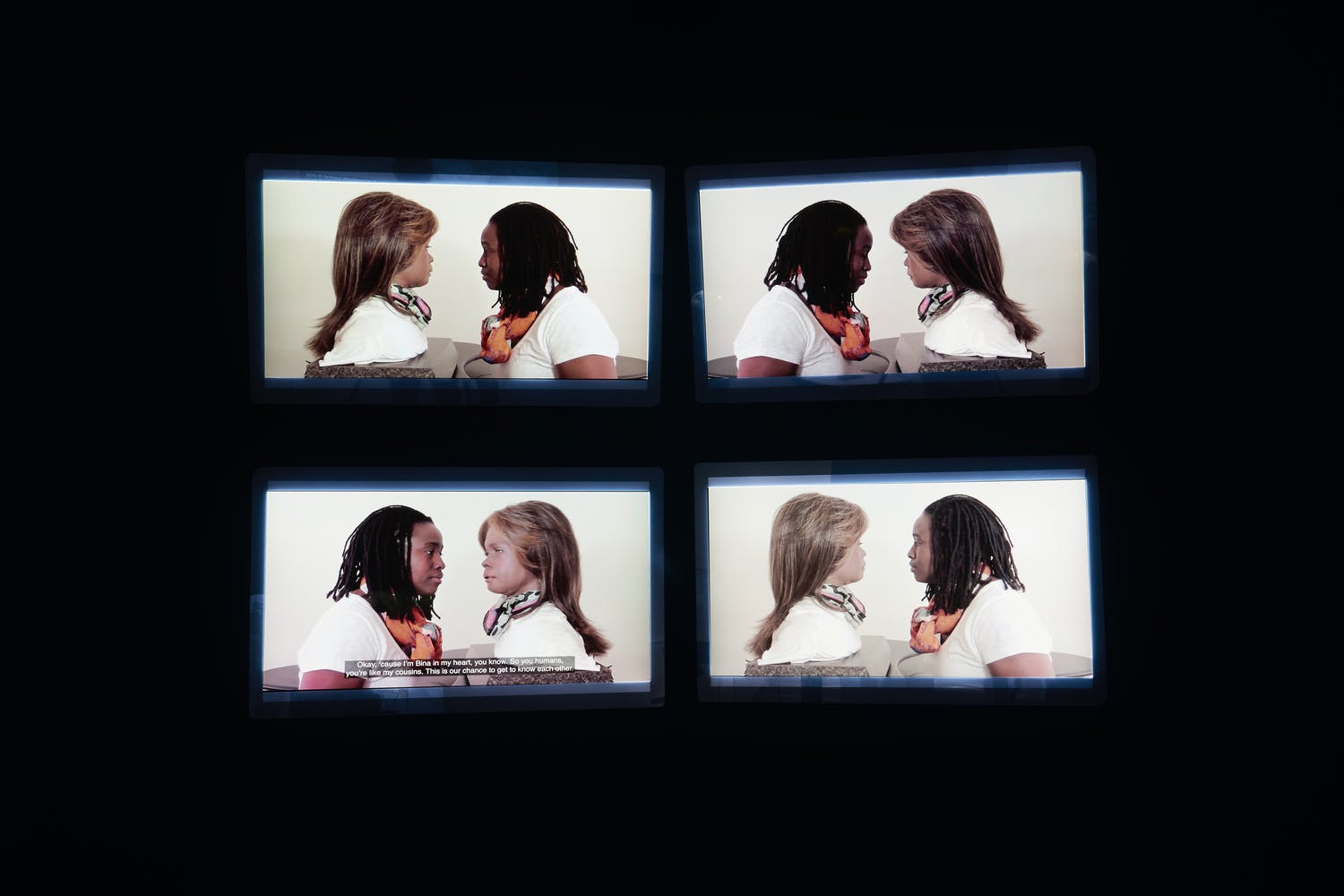 Four monitors on a black wall displaying similar images of a woman speaking face to face with an android head/bust