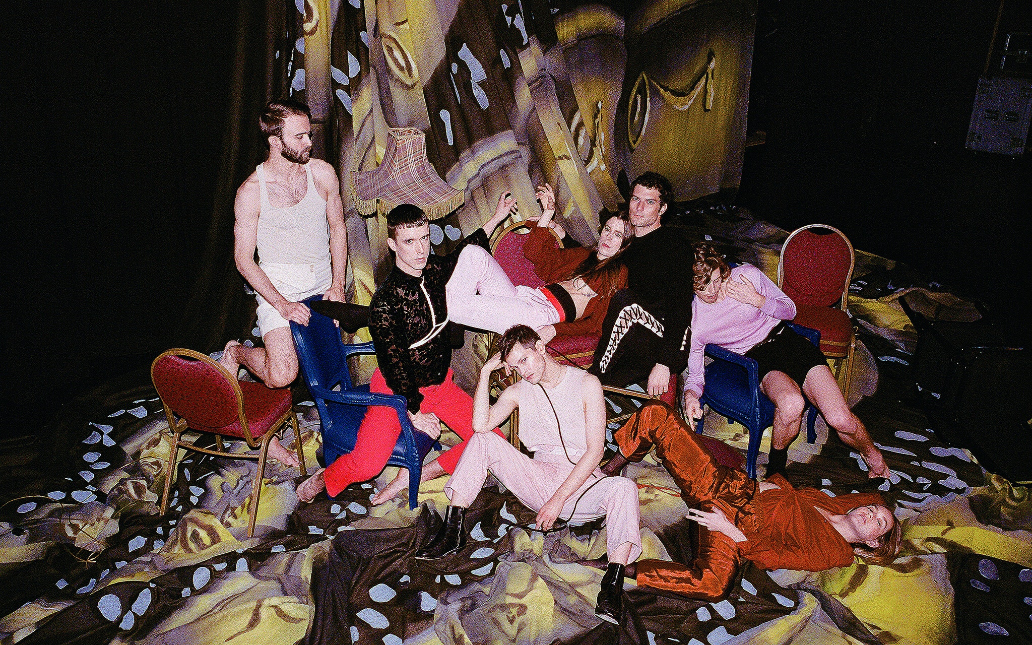 Perfume Genius x Kate Wallich and the YC posing on a multicolored skrim and chairs.