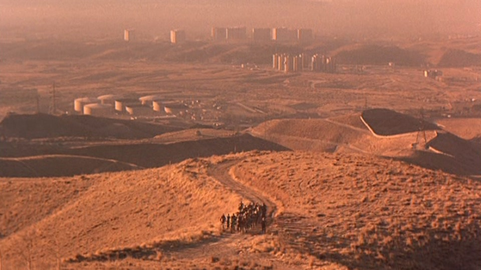 Desert with a city in the background and a group of people walking in the foreground.