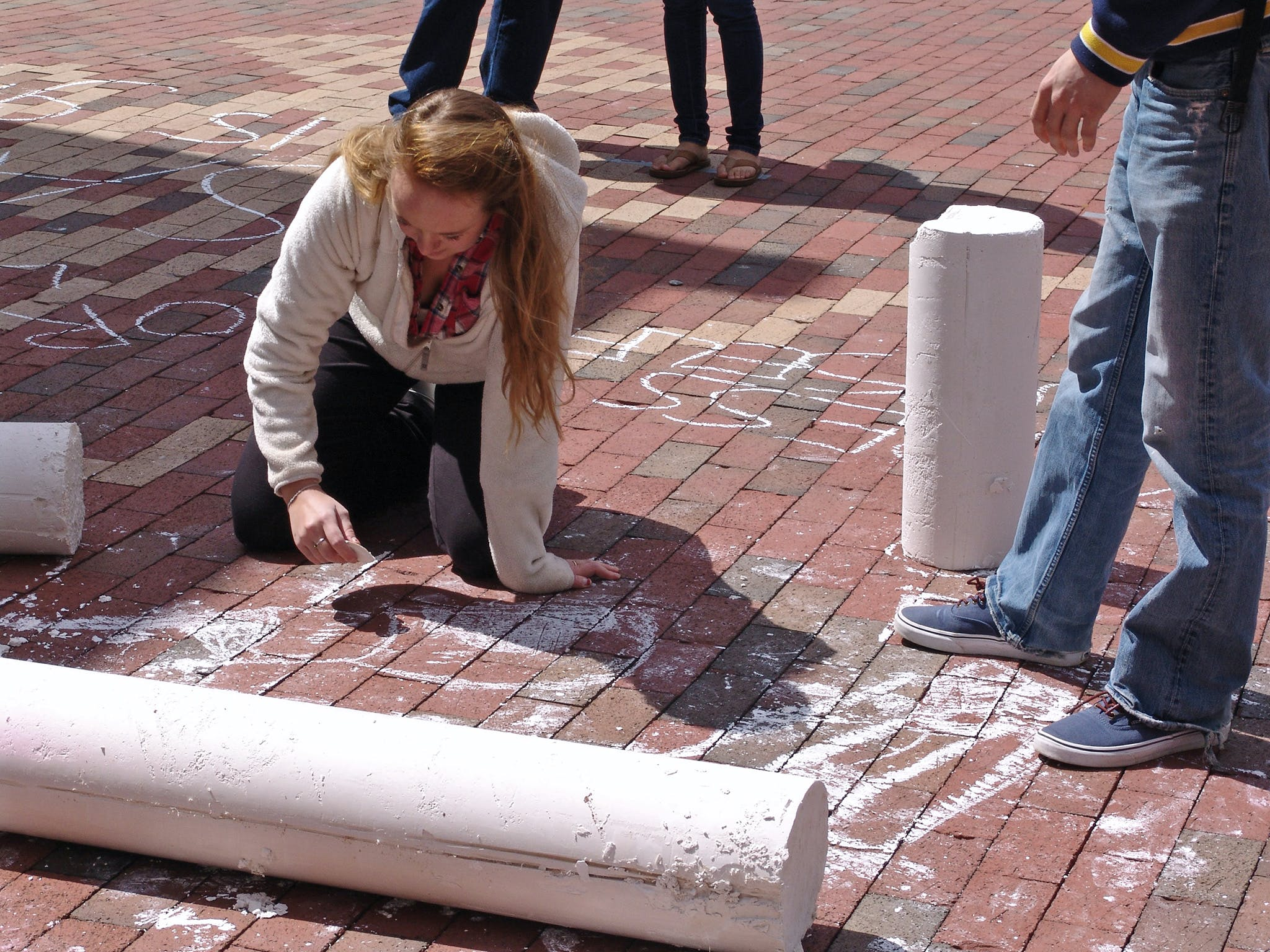 Woman writing on brick ground with white chalk.