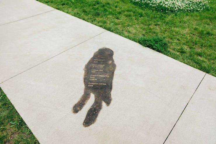 Shadow outline on sidewalk with text of Eliza Winston poem.