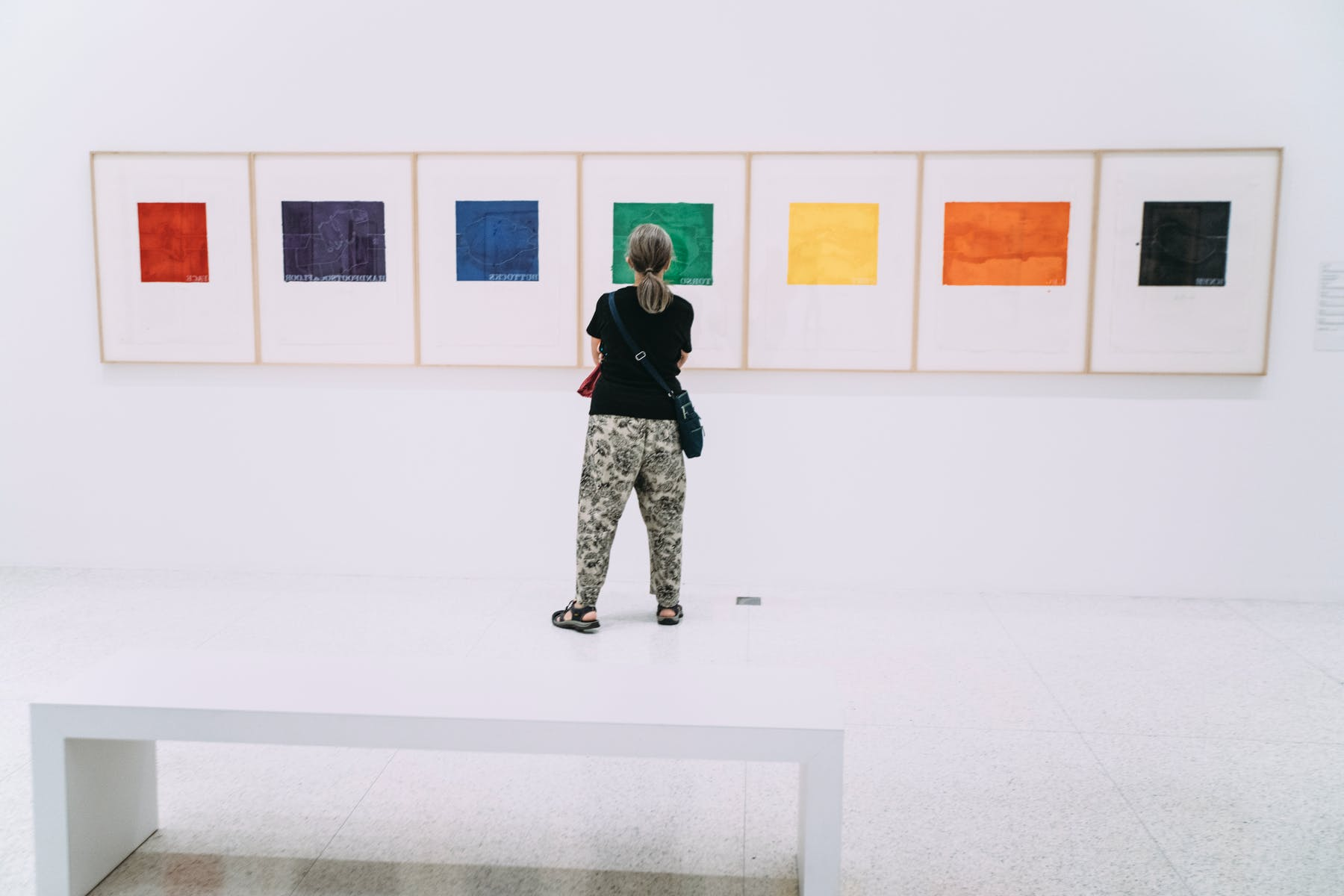 Woman standing in gallery in front of five paintings with colored squares