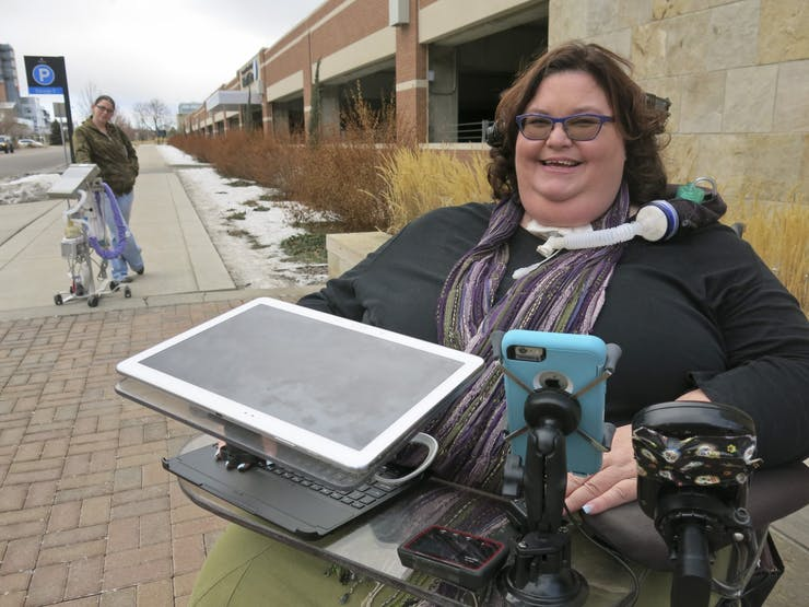 A white wheelchair user with a tracheostomy and tinted glasses smiles on the street. Another person stands in the background with a medical device on wheels.