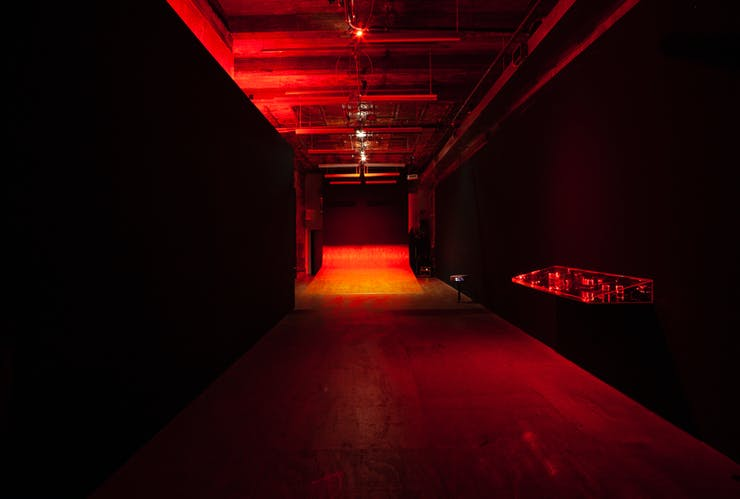 A black room awash in red light. Attached to the wall is a clear display case containing red objects. A plywood ramp extends out from the back wall.