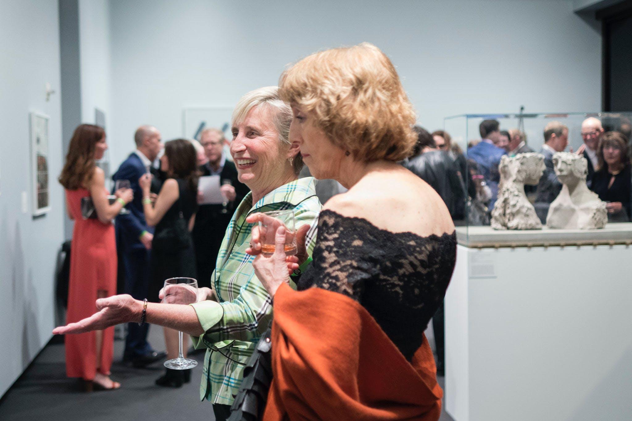 Two women in formal attire viewing exhibit.