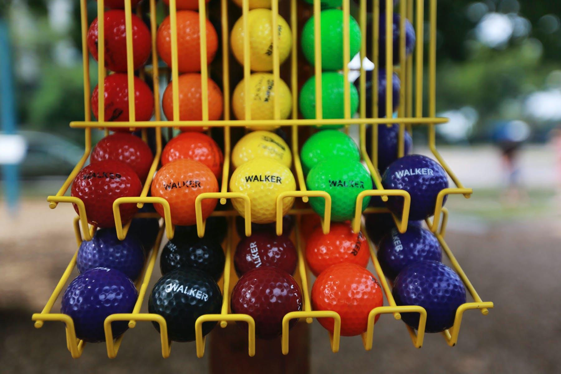 multi-colored golf balls in ball rack.