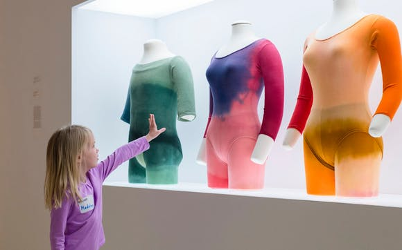 child reaching towards exhibition costumes
