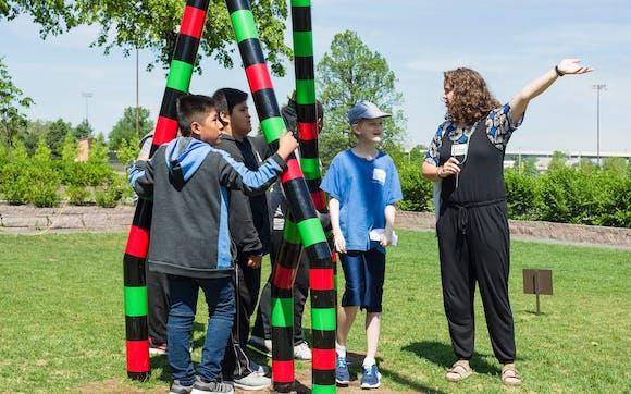 Children and instructor standing near a sclupture in the Minneapolis Sculputre Garden