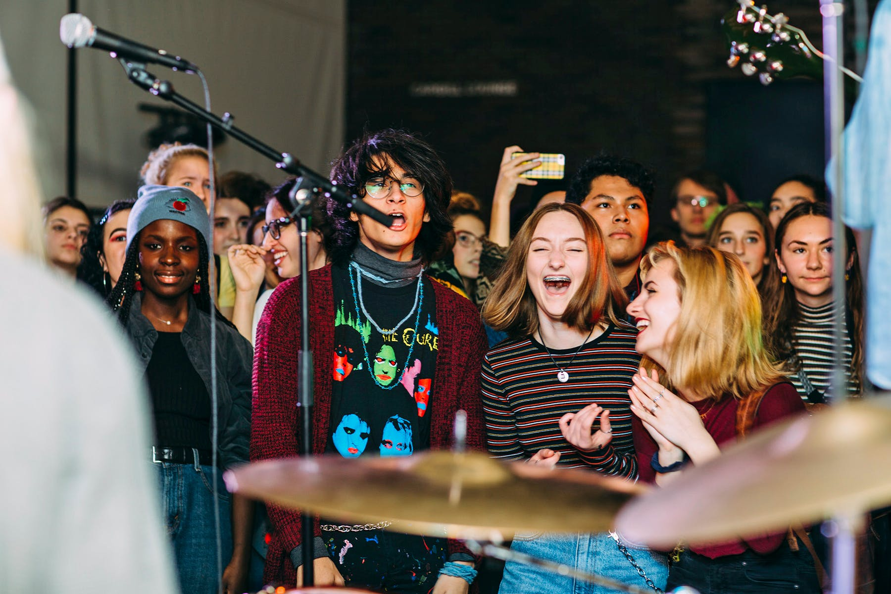 A group of teenagers dancing and singing along to a band.
