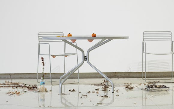 patio table with with two oranges on it