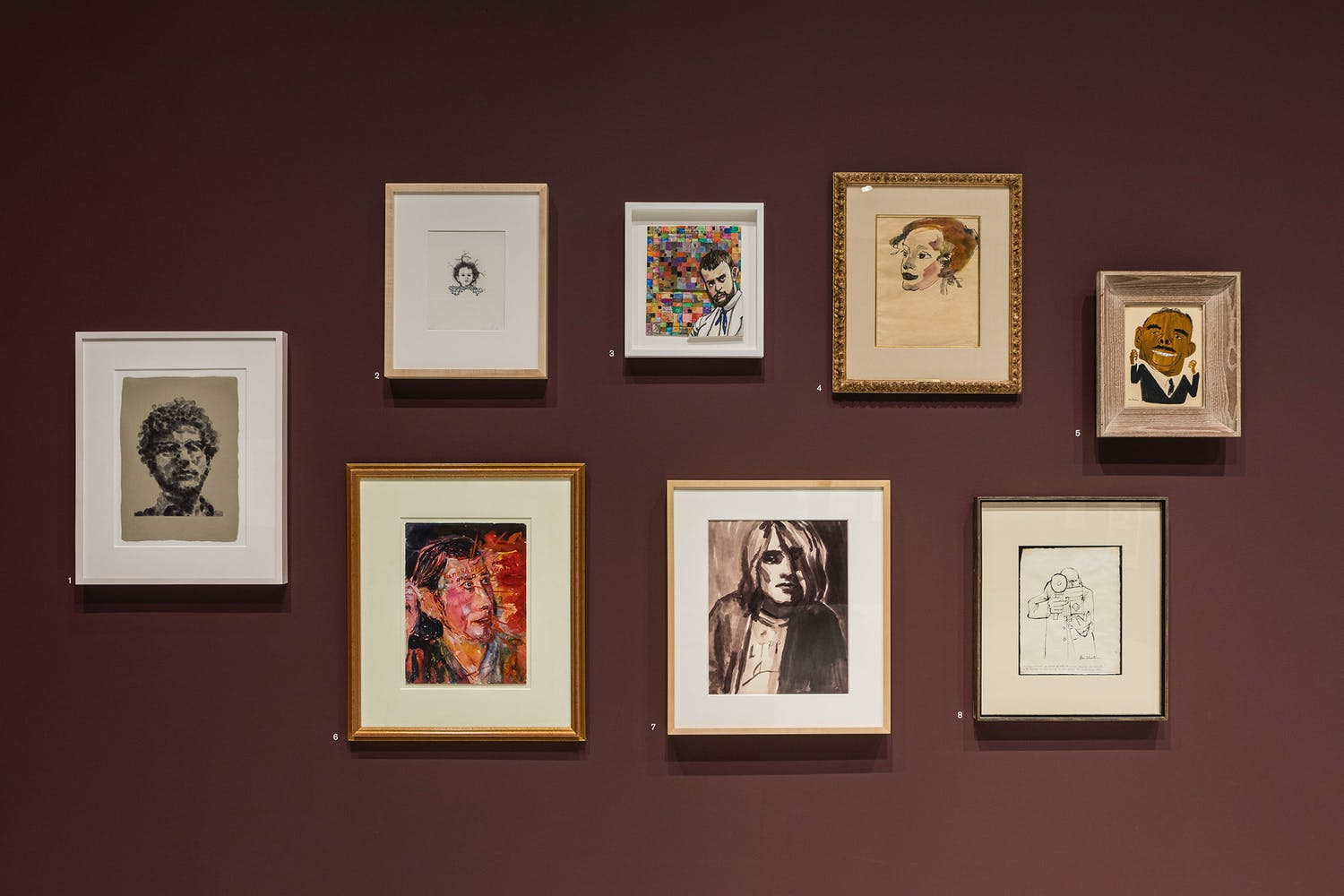 Paintings hung on a brown wall.