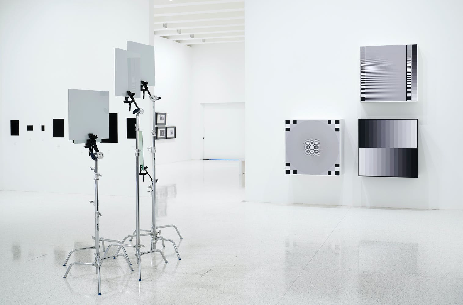 Gallery with black and white geometric paintings on the wall and white cards on metal stands in the center of the room
