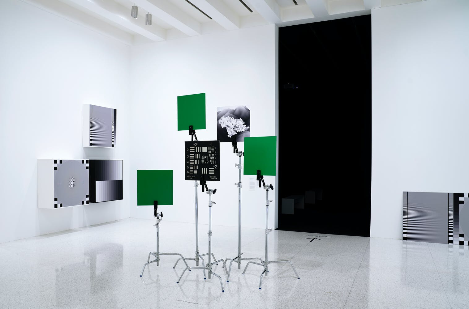 Image of gallery with green cards placed on metal stands in center of room