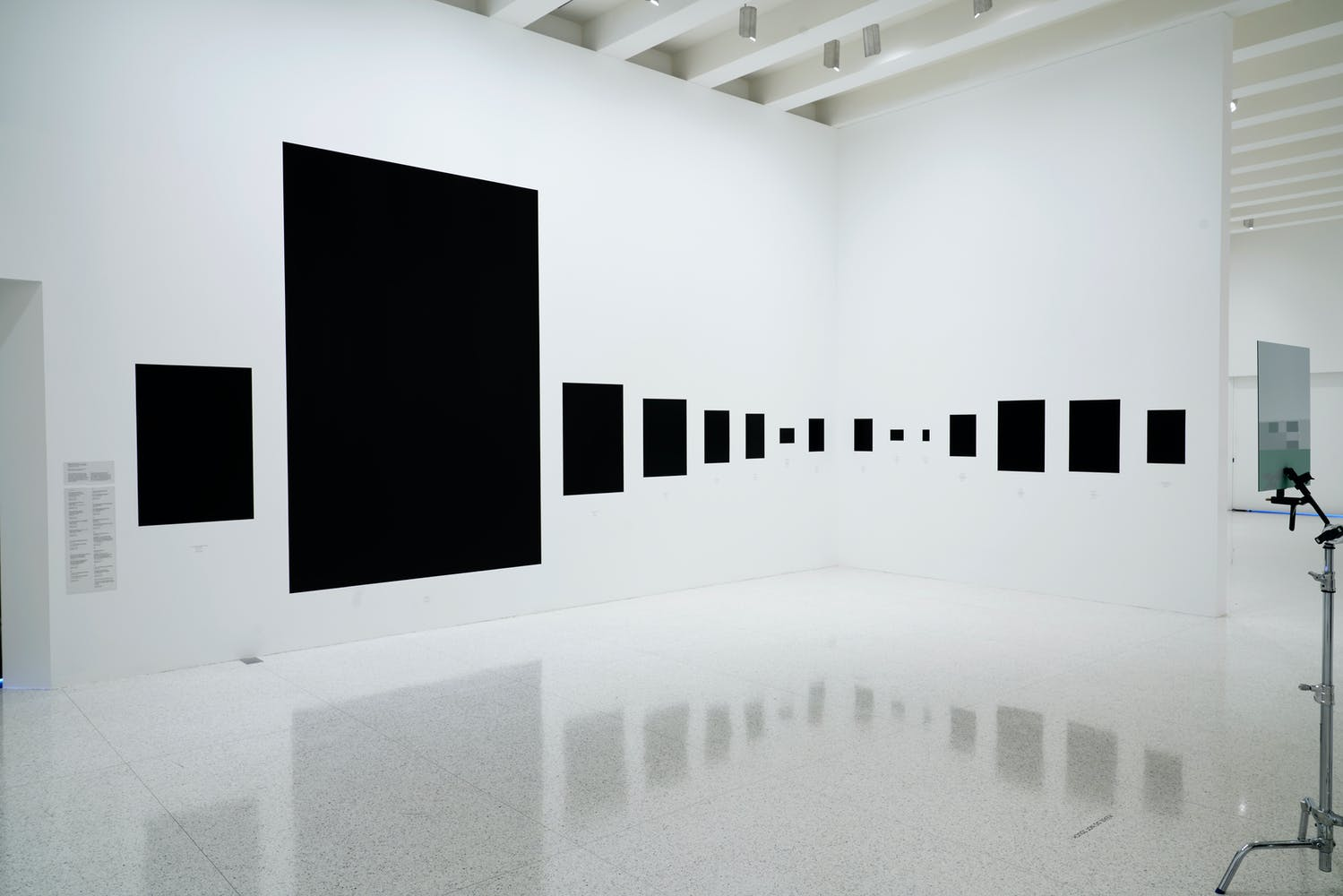 Image of gallery walls featuring large black squares of different sizes printed on them