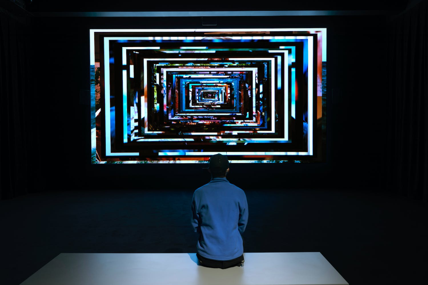 Image in dark room with person on bench watching large projected movie featuring geometric colorful nested rectangles