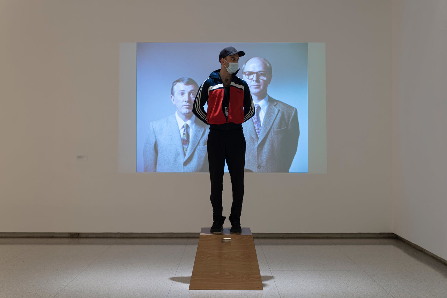 Gallery view with man standing on brown wooden platform with projection in the background