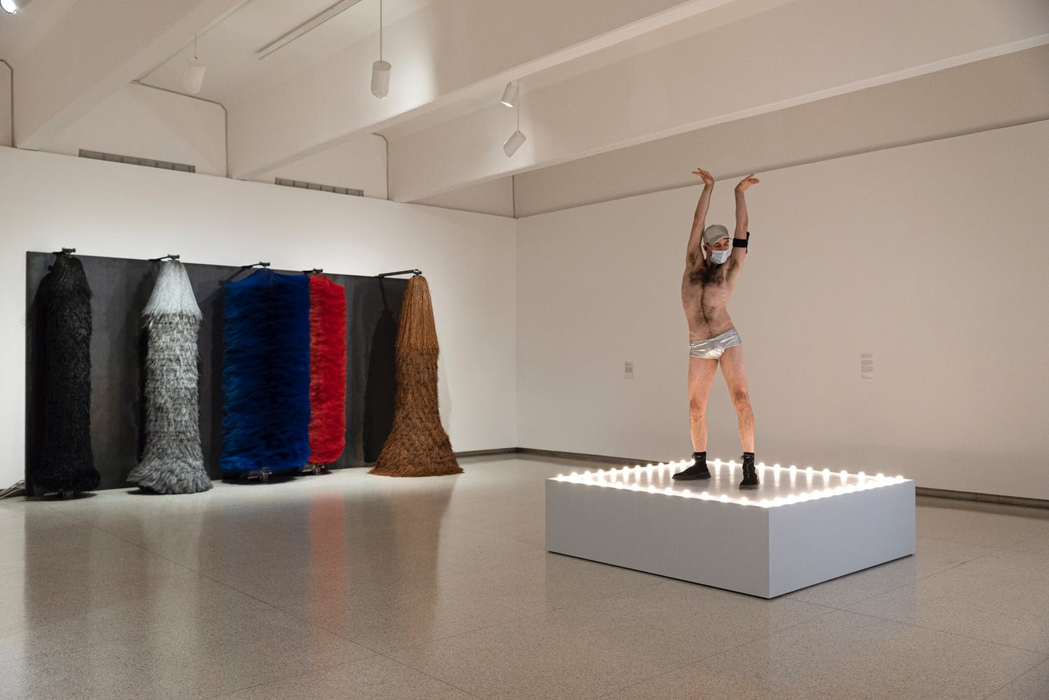 Gallery view with large car wash spinning brushes on wall with man wearing only speedo and shoes dancing on lit platform in foreground