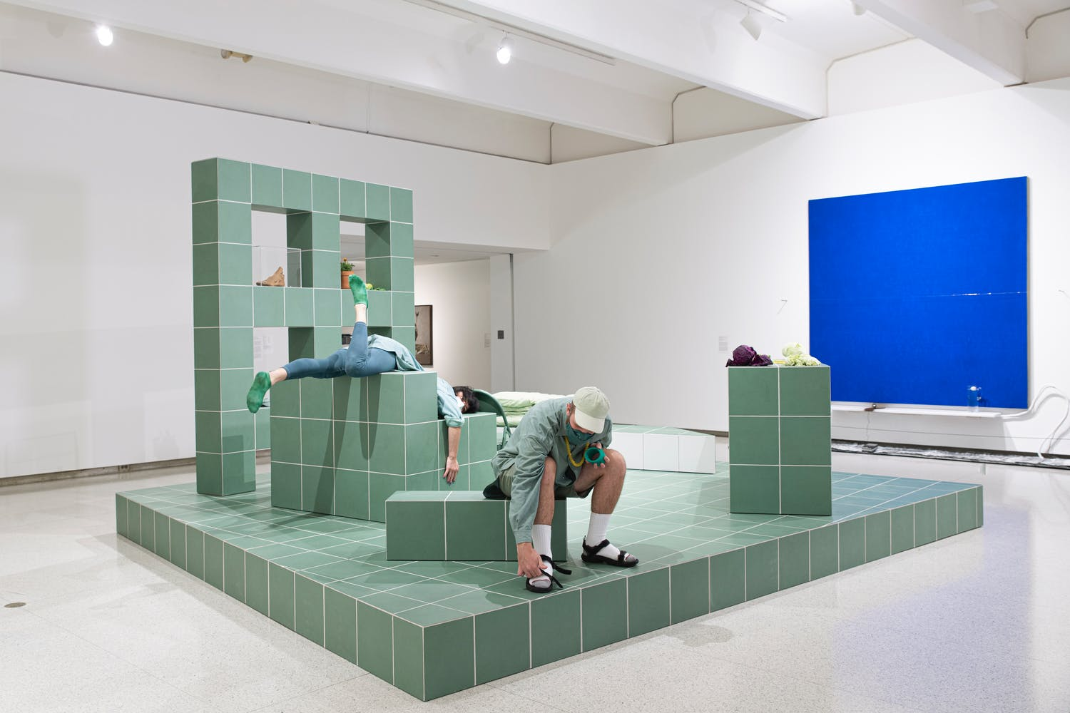 Gallery view with green block like structure and two men performing on it