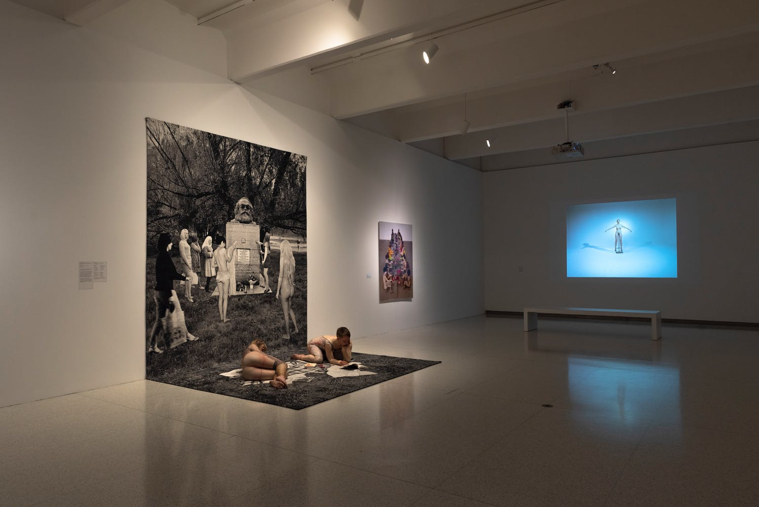 Gallery view of large print out with two performers lying on it and projection in the background