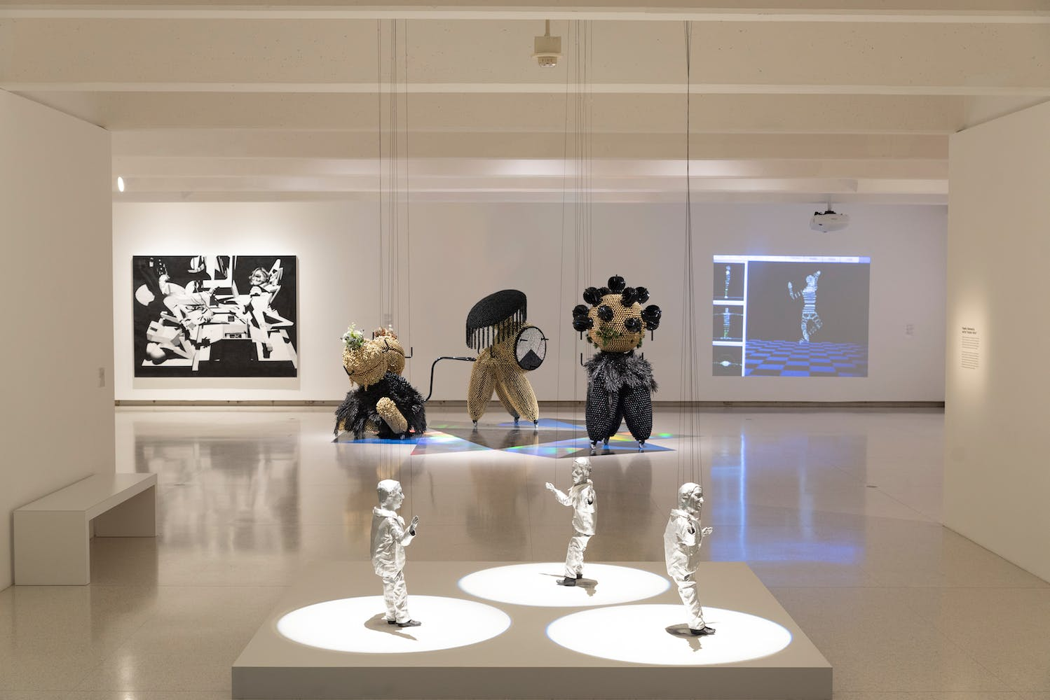 Gallery view with various sculpture objects and projections and paintings
