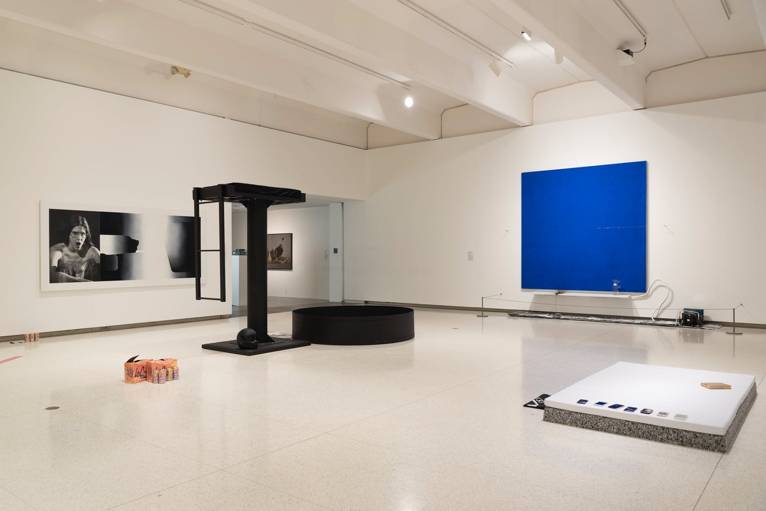 Gallery view with various sculpture objects and paintings